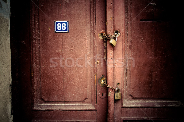 Old rusty padlock and chain on the wooden gate home Stock photo © pixachi