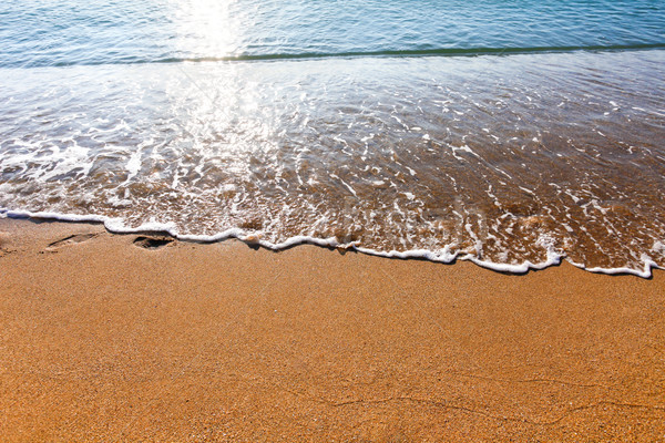 Soft wave of the sea washing foot marks from the sandy beach Stock photo © pixachi