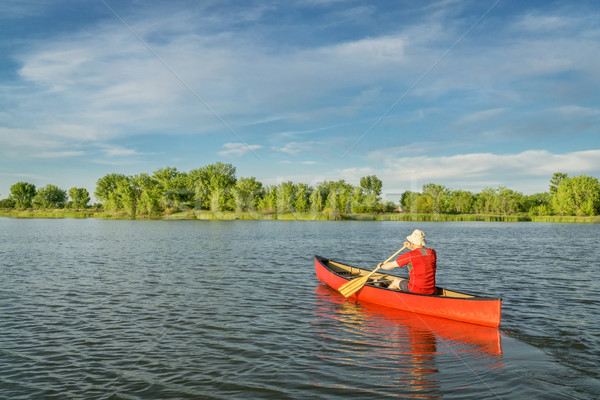 Tarde canoa lago masculino vermelho local Foto stock © PixelsAway