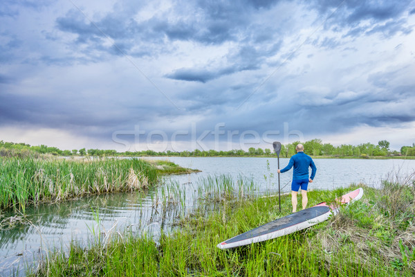 senior paddler with SUP paddleboar watching stormy sky Stock photo © PixelsAway
