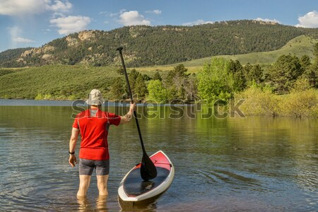 male paddler with SUP paddleboard on lake Stock photo © PixelsAway