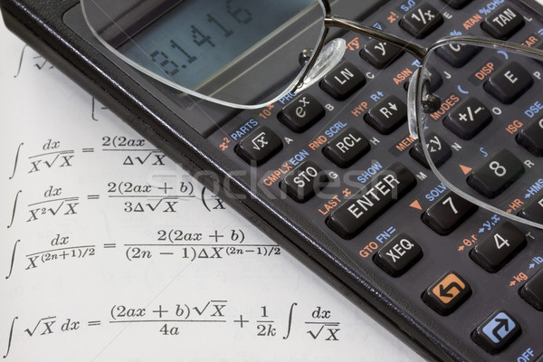 scientific calculator, reading glasses, math book background Stock photo © PixelsAway