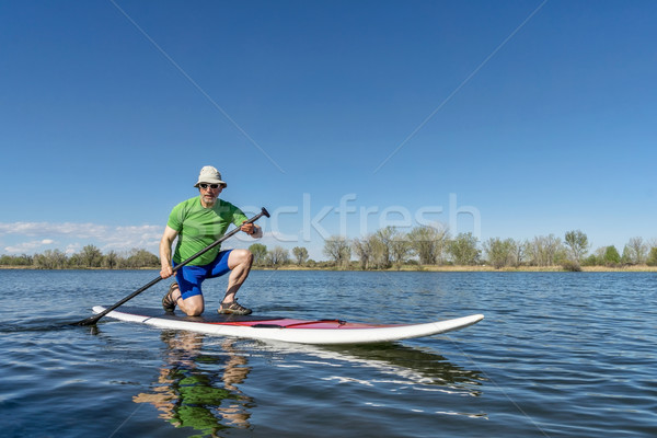 senior male on stand up paddleboard Stock photo © PixelsAway