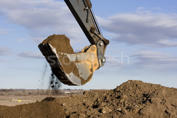 Excavator arm and scoop digging dirt at construction site Stock photo © PixelsAway
