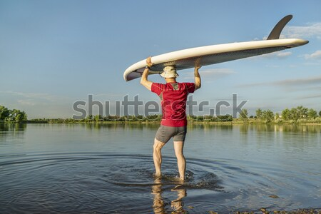 senior paddler carrying paddleboard Stock photo © PixelsAway