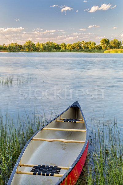 red canoe on lake ready for paddling Stock photo © PixelsAway