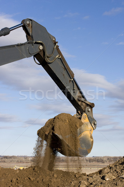 Excavator arm and scoop digging dirt at road construction Stock photo © PixelsAway