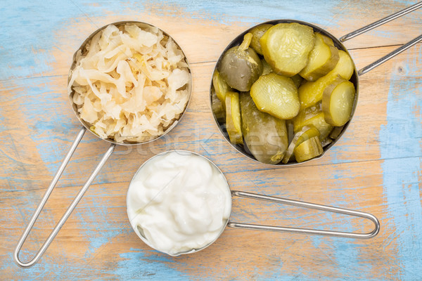 sauerkraut, cucumber pickles and yogurt - popular probiotic fermented food - three measuring cups ag Stock photo © PixelsAway