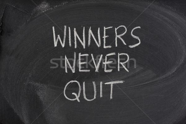 Stock photo: winners never quit phrase on blackboard