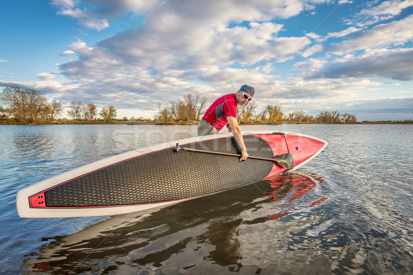 launching stand up paddleboard on lake Stock photo © PixelsAway