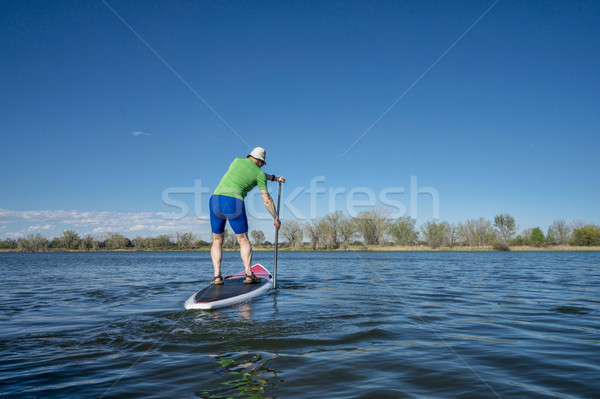 Senior male exercising on SUP paddleboard Stock photo © PixelsAway