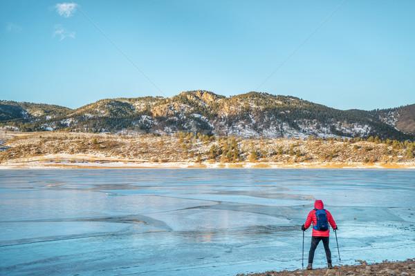 hiker at frozen mountain lake Stock photo © PixelsAway