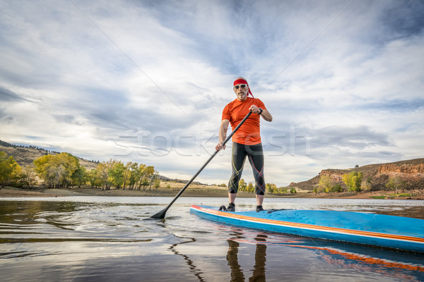 stand up paddling on mountain lake Stock photo © PixelsAway