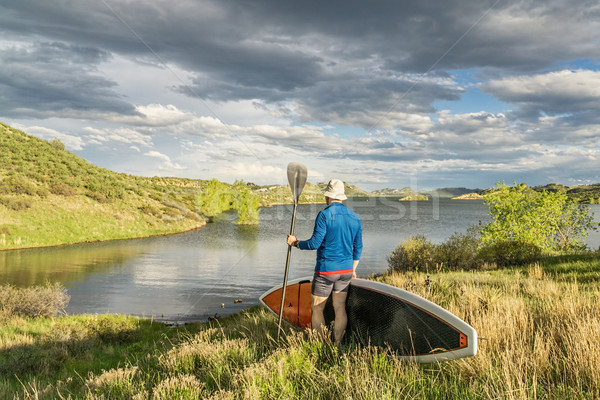 male paddler with stand up paddleboard (SUP) on a grassy shore of mountain lake - Horsetooth Reservo Stock photo © PixelsAway