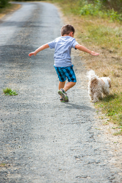 Young child running down the road with small dog Stock photo © pixinoo