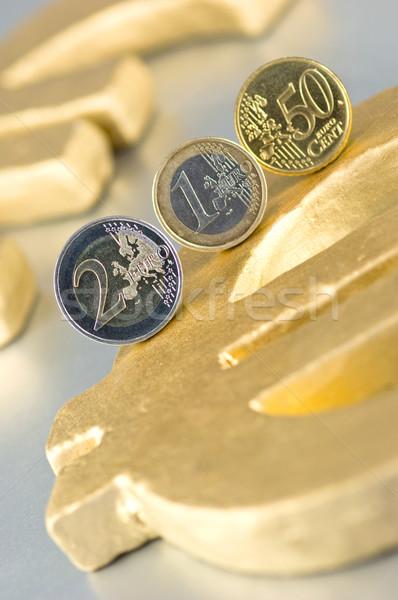 Euro coins on a golden Euro sign Stock photo © pixpack