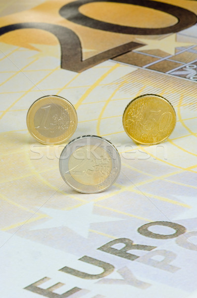 Euro coins rolling over a 200-euro-banknote Stock photo © pixpack