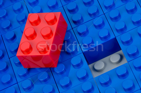 Red building block in a field of blue one Stock photo © pixpack