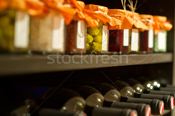 Wine bottles and mason jars in a rack Stock photo © pixpack