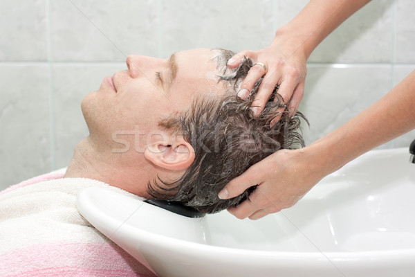 Blonde in a salon getting washed her hair Stock photo © podsolnukh