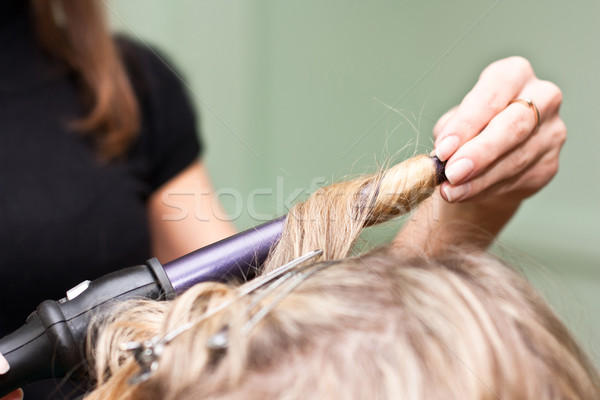 Hairdresser to curl the hair in a beauty salon Stock photo © podsolnukh