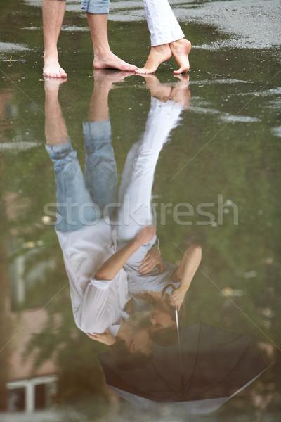 Pocsolya tükröződés pár ölel esernyő víz Stock fotó © pressmaster