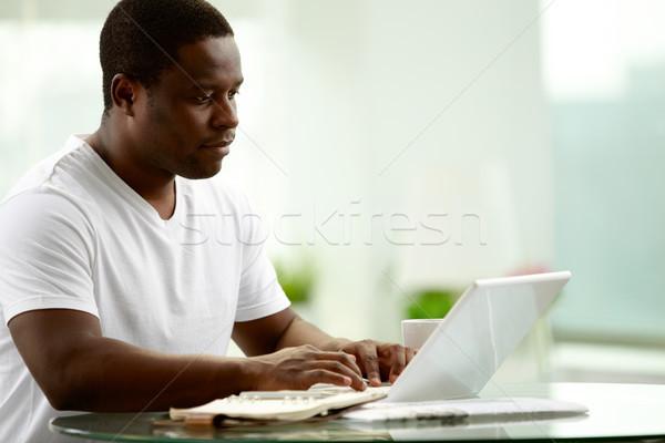 Homem datilografia imagem jovem africano laptop Foto stock © pressmaster