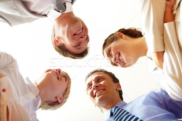 Abaixo ângulo feliz pessoas de negócios olhando negócio Foto stock © pressmaster