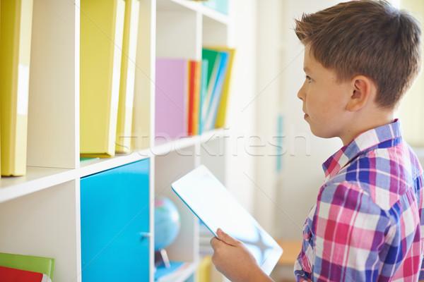 Nino touchpad grave colegial mirando libros Foto stock © pressmaster
