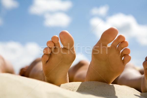 Megnyugtató közelkép kettő emberi napozás homokos tengerpart Stock fotó © pressmaster