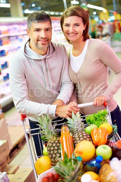 Gelukkig consumenten afbeelding paar winkelwagen vol Stockfoto © pressmaster