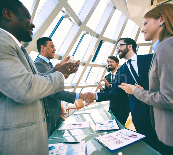 Group of business people clapping their hands while their colleagues handshaking Stock photo © pressmaster