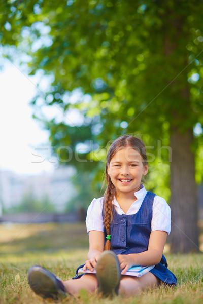 Bastante feliz colegiala sesión parque mirando Foto stock © pressmaster