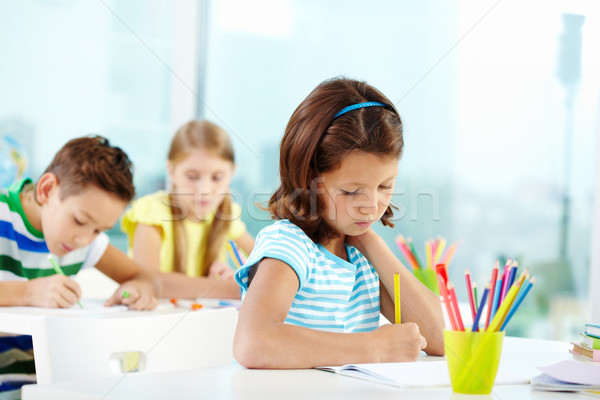 Schoolgirl at drawing lesson Stock photo © pressmaster