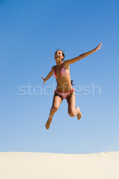 Portrait of joyful girl leaping on sandy beach during summer vacation and laughing Stock photo © pressmaster
