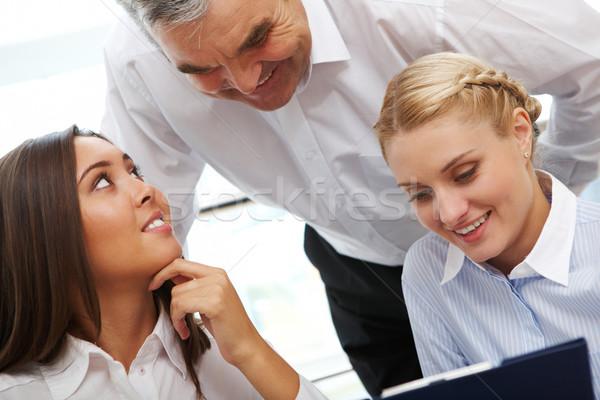 Trabalho em equipe imagem três pessoas de negócios discutir documentos Foto stock © pressmaster
