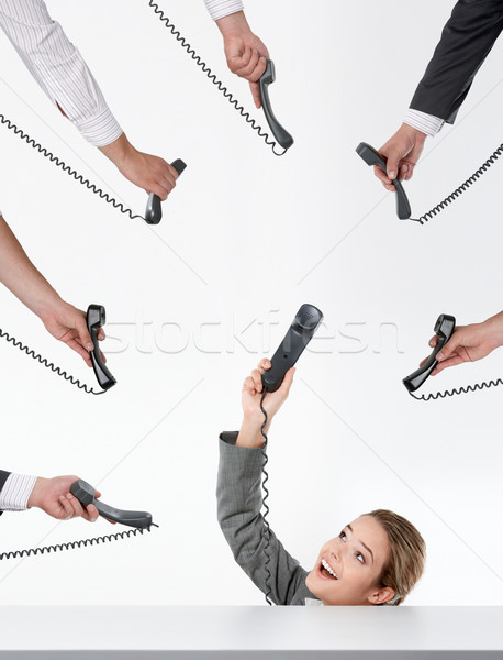 Photo of businesswoman showing her telephone receiver while being offered several more  Stock photo © pressmaster