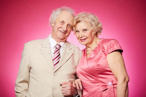 Aposentados casal retrato encantador posando rosa Foto stock © pressmaster