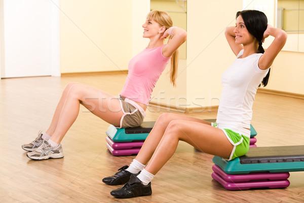 Wykonywania dwa dziewcząt posiedzenia sala gimnastyczna Zdjęcia stock © pressmaster