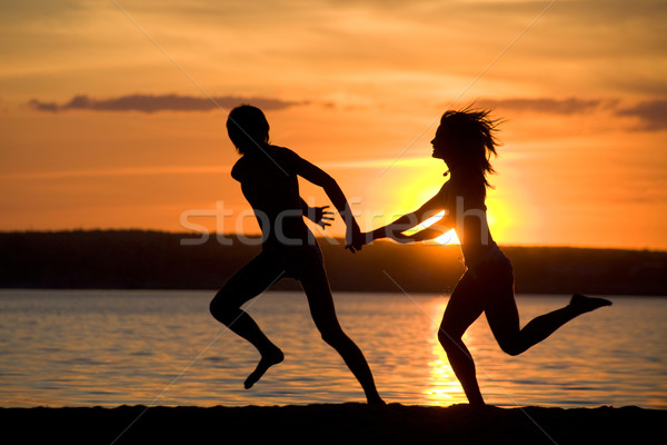 Courir rive silhouettes heureux couple Photo stock © pressmaster