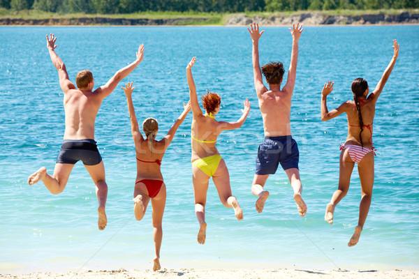 весело озеро группа людей руки вверх прыжки пляж Сток-фото © pressmaster