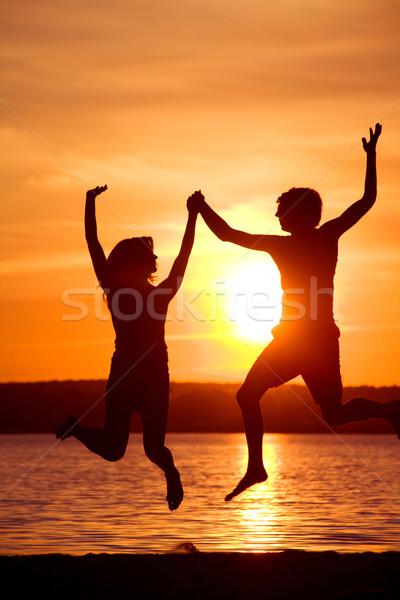 Dinamizmus sziluettek boldog pár ugrik kiemelt Stock fotó © pressmaster
