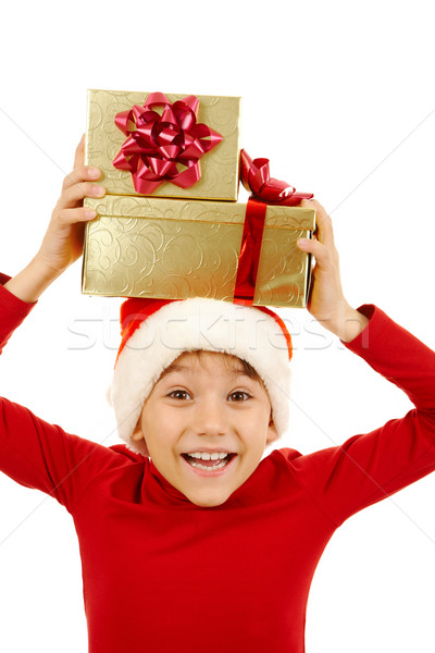 Portrait of happy boy holding giftboxs above his head and expressing surprise Stock photo © pressmaster