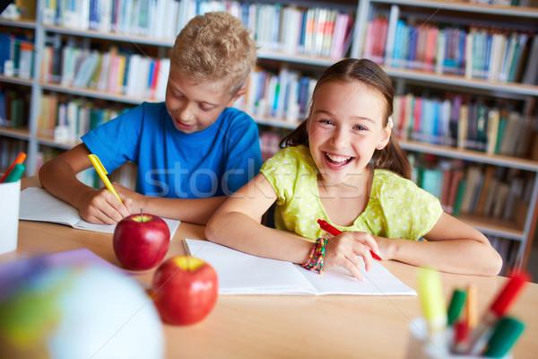 Osztálytársak könyvtár portré derűs iskolás lány néz Stock fotó © pressmaster