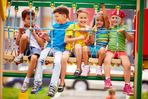 Gyerekek szórakozás boldog barátok hinta játszótér Stock fotó © pressmaster