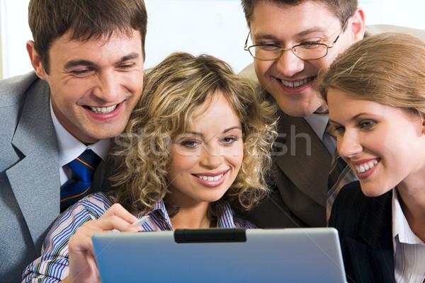 Primer plano cuatro personas sonriendo gente de negocios supervisar portátil Foto stock © pressmaster