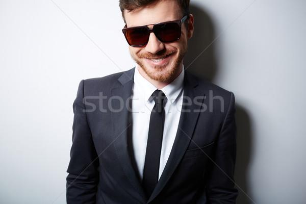 Işadamı güneş gözlüğü serin takım elbise poz izolasyon Stok fotoğraf © pressmaster