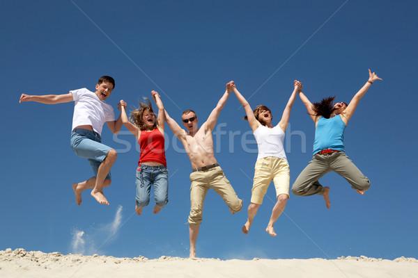 Stock fotó: Dinamizmus · fotó · izgatott · emberek · ugrik · homokos · tengerpart