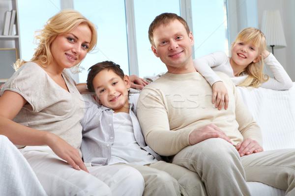 Maison de famille jeunes famille quatre séance canapé Photo stock © pressmaster