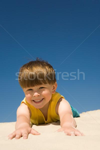 Przyjemny piasku patrząc kamery uśmiech Zdjęcia stock © pressmaster